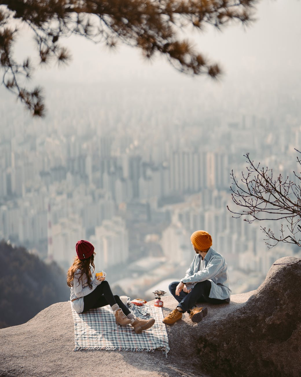 man and woman sitting on rock